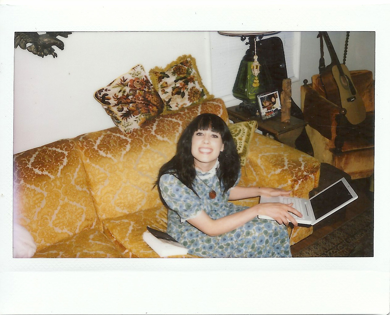 The blogger, Nikki Leigh, working on her favorite orange velvet couch.
