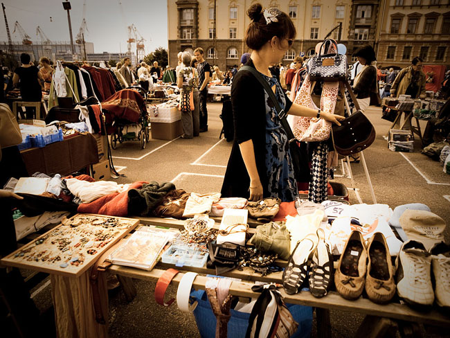 Woman shopping for vintage clothing at a stylish flea market. Read about where to shop for vintage treasures at differentdrumblog.com